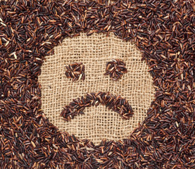 Red rice forming a sad face on burlap fabric
