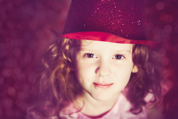 Close-up portrait of a little girl in shiny red hat. Instagram f
