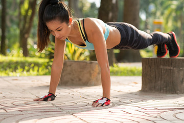 Fit girl doing straight arm plank exercise, her legs on stump
