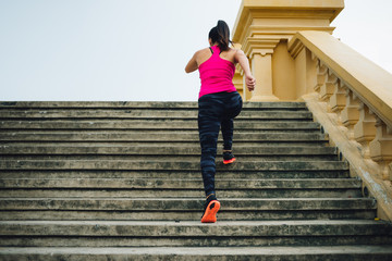 Rear view of female athlete running up the stairs