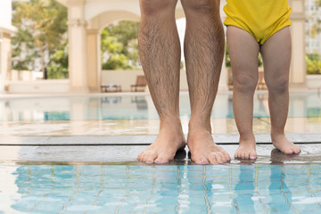 Man with little son standing at poolside