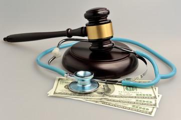 Stethoscope with judge gavel, money on gray background