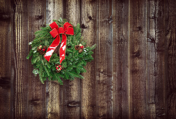 Christmas wreath against rustic wooden background