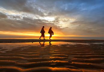 Monks walk on the beach