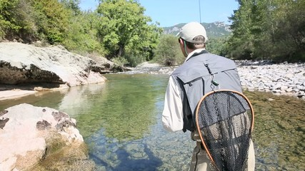 Fisherman fly fishing in trout river