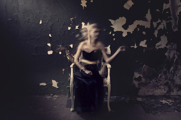 Ghost woman in black on a chair. Grunge room