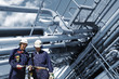 oil and gas workers with giant pipelines constructions