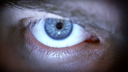 Closeup of blue male eye with contact lens looking at camera.