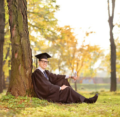 Graduate student sitting by a tree in a park