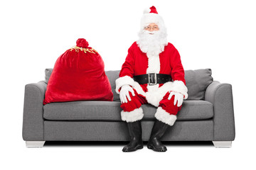 Santa sitting on a sofa with bag of presents