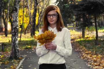 girl teen with autumn leaves in the hands