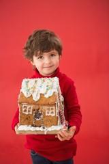 Festive little boy holding gingerbread house