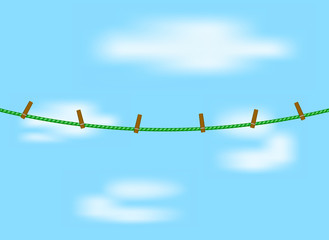 Clothespins on green rope and blue sky