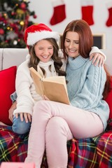 Festive mother and daughter reading on the couch