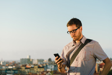 Professional casual man checking messages on smartphone