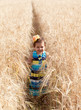 Joyful little girl runs on a wheat field