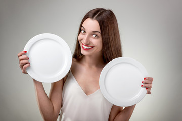 Young woman showing empty plates.