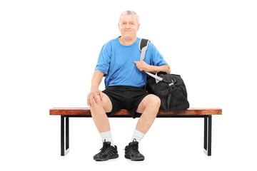 Active senior carrying a sports bag seated on bench