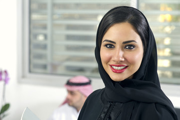 Arabian Businesswoman wearing hijab with her boss in background