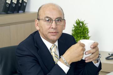 Senior Businessman drinking coffee in office