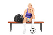 Female soccer player sitting on a bench