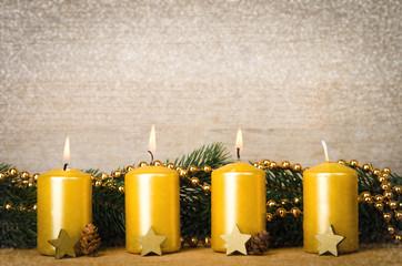 3 goldene adventskerzen mit schnee