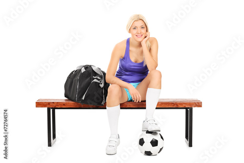 canvas print picture Female soccer player sitting on a bench