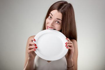 Young woman bites empty plate.