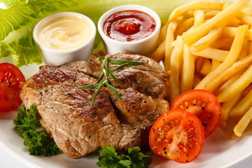 Barbecued steak, French fries and vegetables