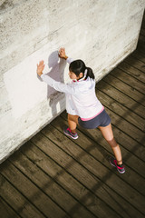 Asian athlete stretching legs before running