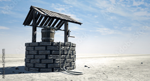 Poster Zandwoestijn Wishing Well With Wooden Bucket On A Barren Landscape
