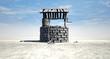 Leinwandbild Motiv Wishing Well With Wooden Bucket On A Barren Landscape
