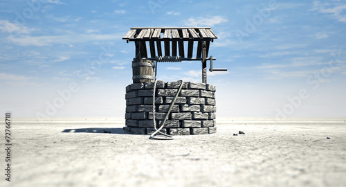 Wishing Well With Wooden Bucket On A Barren Landscape - 72766718