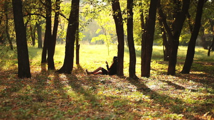 Young girl resting in maple grove in fall
