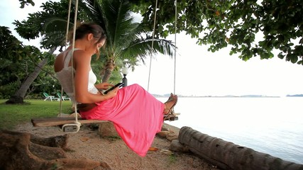 Woman on a swing at palm tree and talking by phone. Koh Samui,