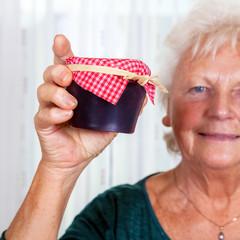 Grandma holds up her homemade jam
