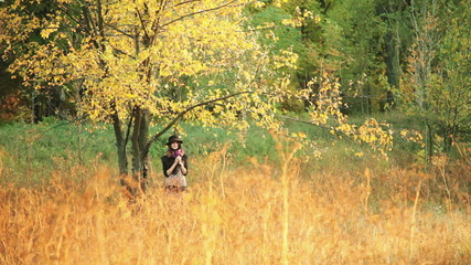 young girl on the meadow under a tree