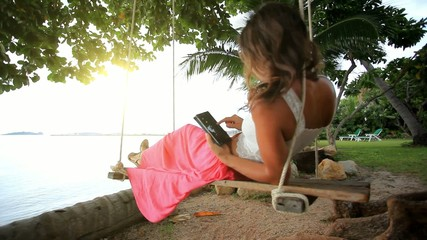 Woman on a swing at palm tree uses smartphone and talking by