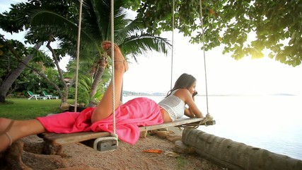 Woman lies on a swing at palm tree and talking by phone. Koh