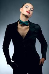 Красивая брюнетка в костюме на сером фоне
