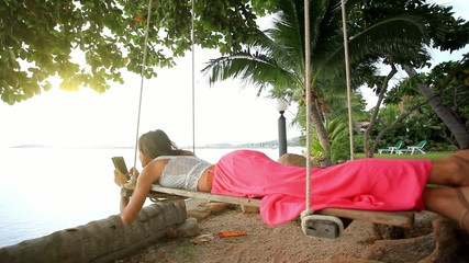 Woman lies on a swing at palm tree uses smartphone and takes