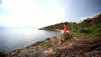 Young woman standing on a rockis taking photo. Koh Samui.