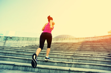 young fitness woman running up on stairs