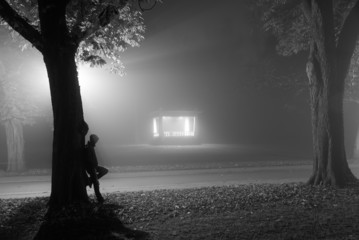 Man leaning agianst a tree in a foggy park at night.