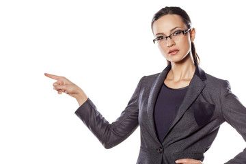 Positive business woman shows with her fingers in the blank