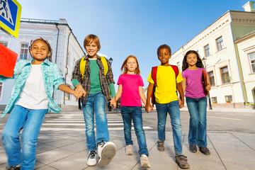 International children wear bags and walk in row