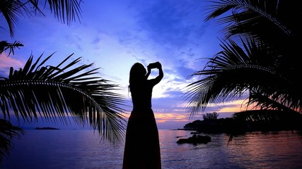 Woman Takes photo view by phone at sunset time. Koh Samui.