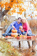 Young family near lake with pumpkins, autumn time