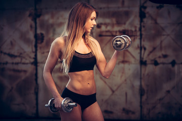 attractive young woman working out with dumbbells in an abandone