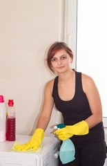 Young housewife dusting in bathroom
